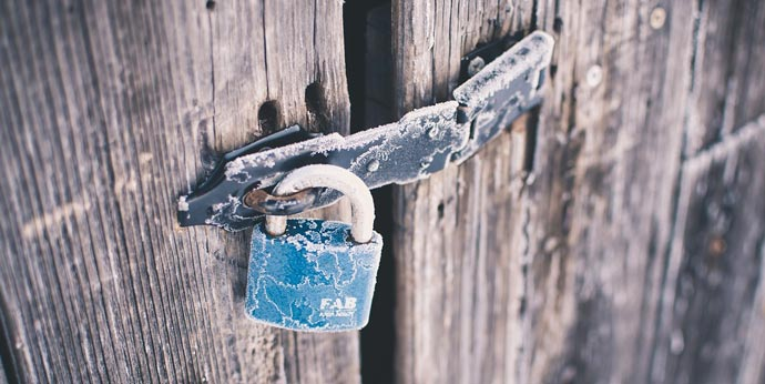 securely locked padlock on wooden gate