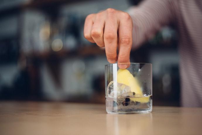 man placing lemon in drink