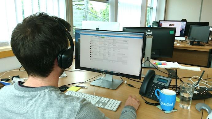 man wearing headset working at desktop computer